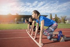 Women ready to race on track field Royalty Free Stock Image