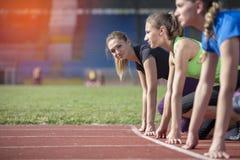 Women ready to race on track field Stock Photo