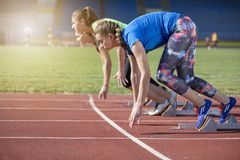 Women ready to race on track field Royalty Free Stock Photography