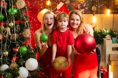 Women red dresses celebrate christmas with little cute baby. Family bonds. Love peace joy. Kid boy with mom or aunts. Sisters having fun. Join celebration stock image