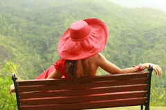 Women with red hat on the bench. Woman and tropical forest  nature landscape Seychelles Islands Beauty in the woods Seychelles. Dreaming Royalty Free Stock Photos