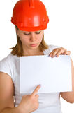 Women in a red helmet shows on a sheet of paper Stock Photography