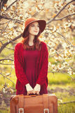 Women in red sweater and hat with suitcase Stock Images