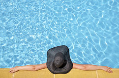 Women in a relaxed position in the pool with pamel Royalty Free Stock Image