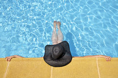 Women in a relaxed position in the pool with pamel Stock Photos