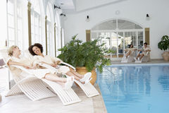 Women Relaxing Around Pool At Spa. Smiling at each other royalty free stock image