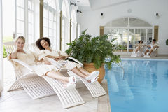 Women Relaxing Around Pool At Spa. Smiling at camera royalty free stock photos
