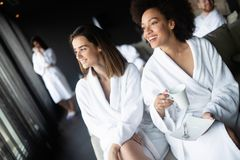 Women relaxing and drinking tea in robes during wellness weekend stock photography