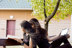 Women relaxing on a garden bench Stock Images