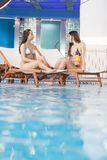 Women relaxing by the pool Stock Photos
