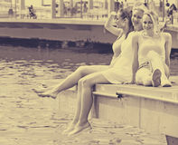 Women resting on esplanade. Portrait of three cheerful young friends resting together on esplanade in european city Royalty Free Stock Photos