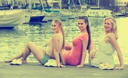 Women resting on esplanade. Portrait of three happy young women resting together on esplanade in european city Stock Image