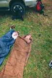 Women resting inside of sleeping bags with 4x4 on Stock Photo