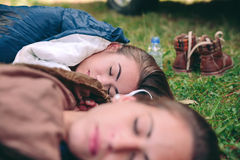 Women resting in the nature inside of sleeping. Closeup of young beautiful women friends sleeping in the nature inside of sleeping bags over the grass. Focus on Royalty Free Stock Image