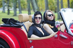 Women at retro car with dark glasses Stock Photography