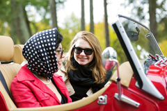 Women at retro car take interesting dialog Stock Image
