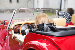 Women at retro red car from behind Stock Image