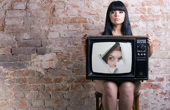Women and retro TV. TV with a picture of the girl -facing through a hole in the hands of a seated women Royalty Free Stock Images
