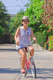 Women ride bicycle in the village Royalty Free Stock Images
