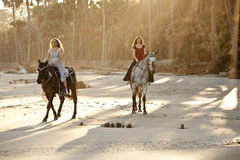 Women riding horses on the beach Royalty Free Stock Images