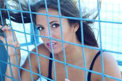 Women rights restriction girl in prison metal grid fence Royalty Free Stock Images