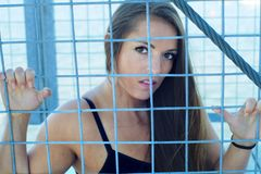 Women rights restriction girl in prison metal grid fence Stock Images
