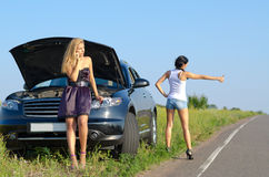 Women with a roadside breakdown. Telephoning for assistance and standing with a thumb out hitchhiking Stock Photo