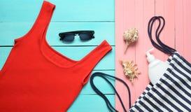 Women& x27; ropa y accesorios de s para la relajación en la playa en un fondo en colores pastel de madera Camiseta foto de archivo libre de regalías
