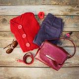 Women& x27; ropa y accesorios del otoño de s: suéter rojo, pantalones, bolso, gotas, gafas de sol, esmalte de uñas, banda del pel Fotos de archivo libres de regalías