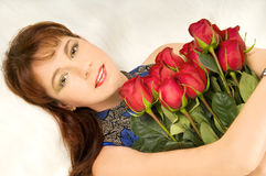 Women and roses. The beautiful woman lays on white to fur,   on her a breast a bouquet of red roses Stock Photos