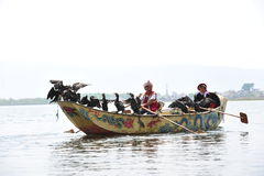 Women rowing a boat fishing by the bird, The Ethnic minority Stock Images