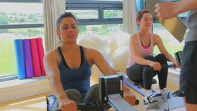 Women at the rowing machine supporting by a coach Royalty Free Stock Images