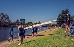 The women rowing team prepare to start with their boat on the bank of Yarra river.  stock photography