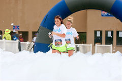 Women Run Through Blanket Of Foam At Race Finish Line Stock Photography