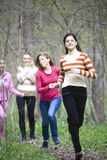 Women running. Four young women running together in forest, smiling Royalty Free Stock Image