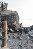 Women running on a beach with boulders in the back. Women running on a dark rocky beach with large boulders and a wooden fence in the background stock photos