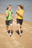Women running on beach laughing. Two women laughing and talking while they run on the beach Stock Photo