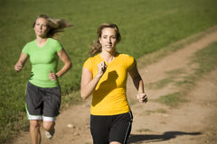 Women running on country road. Two women running down a country road Stock Photos