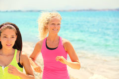 Women running fitness jogging on summer beach royalty free stock image
