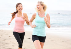 Women running jogging training happy on beach. As part of healthy lifestyle. Two fit female runners talking happy and smiling during workout. Multiracial Asian stock image