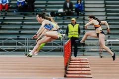 women running race in 100 meter hurdles stock photos