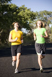 Women running on road. Two women running on a black top road Stock Images