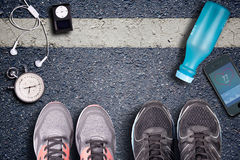 Women Running shoes and equipment on asphalt.  Running training on hard surfaces. Runner Equipment stopwatch and music player. Royalty Free Stock Photos