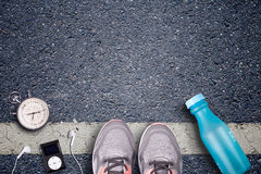 Women Running shoes and runner equipment on asphalt. Training on hard surfaces. Runner Equipment. Stopwatch and music player. The necessary water bottle Royalty Free Stock Images
