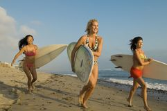Women Running With Surfboards Stock Photos
