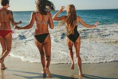 Women running towards the sea to take a dip. Rear view of three girlfriends in bikini walking on beach towards the sea. Women on vacation running towards the sea stock photo