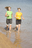 Women running in water. Two women running in the water without shoes and enjoying themselves Royalty Free Stock Image
