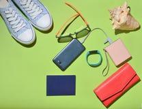 Women' s时髦旅行辅助部件和技术小配件绿色表面上 运动鞋,护照,钱包,玻璃,智能手机 库存照片