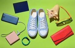 Women& x27; s时髦旅行辅助部件和技术小配件绿色表面上 运动鞋,护照,钱包,玻璃,智能手机 库存照片