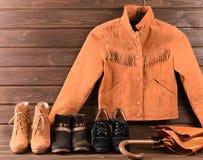 Women& x27; s衣物和辅助部件 布朗绒面革夹克、三双不同鞋和伞 免版税库存照片